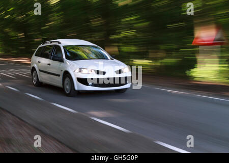 Speeding white car with motion look on a road coming out of the forest in the sunlight - Stock Photo