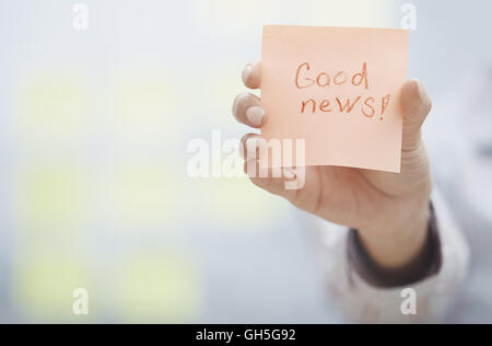 Woman holding sticky note with Good news text - Stock Photo