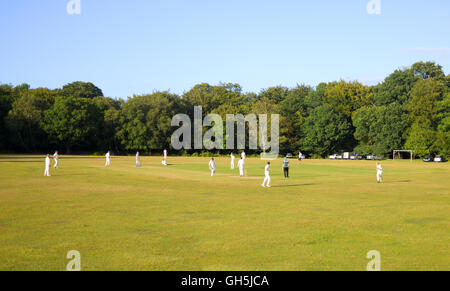 Cricket, a very English game, played in the traditional setting of a village green. - Stock Photo