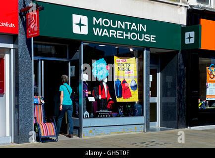 Woman walking into a branch of Mountain Warehouse, England UK - Stock Photo