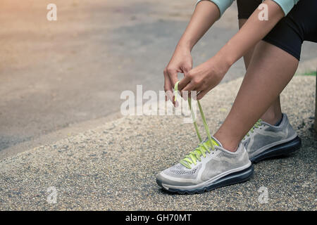 Running shoes - closeup of woman tying shoe laces. Female sport fitness runner getting ready for jogging outdoors - Stock Photo