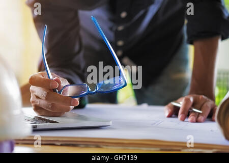 Creative architect projecting on the big drawings in the outdoor office site working area. - Stock Photo