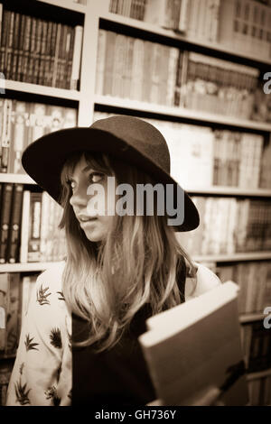 Sepia photograph of a 12 year old blonde Caucasian  girl wearing a black hat in a comic book store holding 2 Manga - Stock Photo