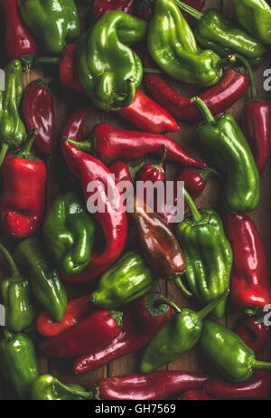 Background of colorful red and green bell peppers over wooden backdrop - Stock Photo