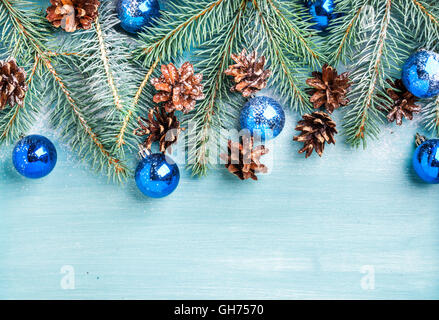 New Year or Christmas background: fir branches, blue glass balls and pine cones over turquoise wooden backdrop, - Stock Photo