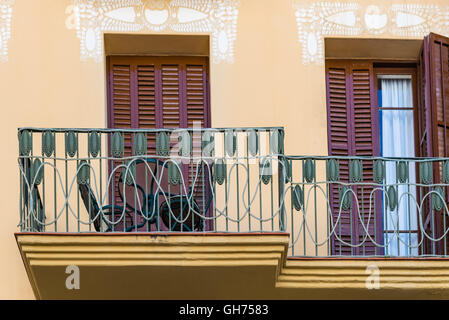 Detail of green metal railings on cute little balcony and brown shutters in front of doors - Stock Photo