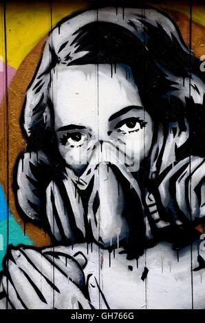 Street art wall mural graffiti of woman wearing oxygen gas mask London England - Stock Photo