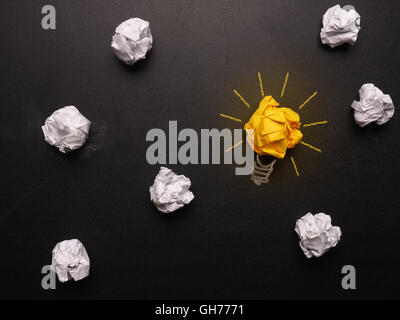 Crumpled paper on a chalkboard with a light bulb