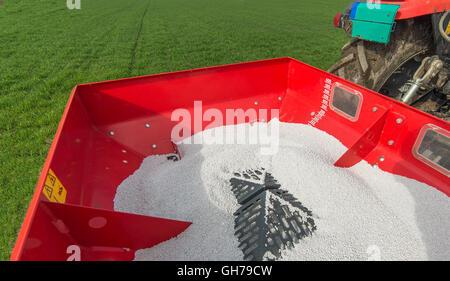 tractor fertilizing in wheat field - Stock Photo
