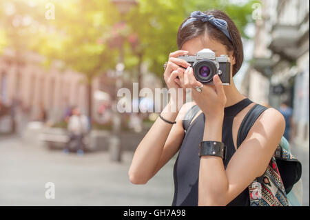 Pretty young female tourist taking pictures in the city - Stock Photo