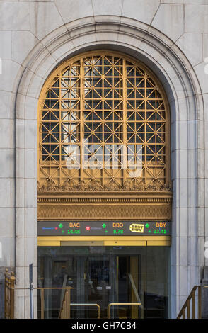 Entrance to New York Stock Exchange at 11 Wall Street, showing digital ticker tape display - Stock Photo