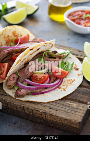 Steak tacos with sliced meet, salad and tomato salsa - Stock Photo