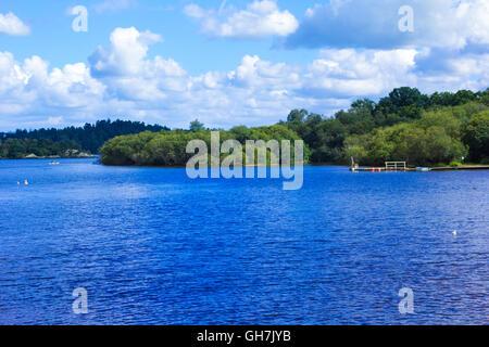 People rowing canoe paddling in calm blue Loch Lomond lake in Scotland