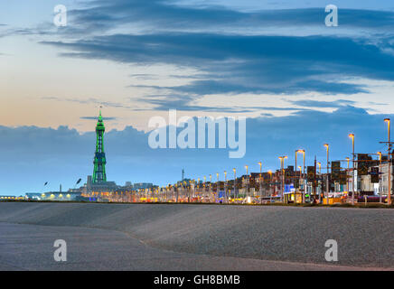 Blackpool tower illuminated in green light at the end of promenade. - Stock Photo