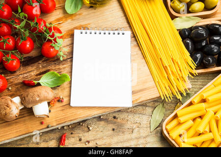 Italian spaghetti pasta with ingredients and recipe notebook .Basil,oregano, mushrooms, tomatoes, olive oil and - Stock Photo