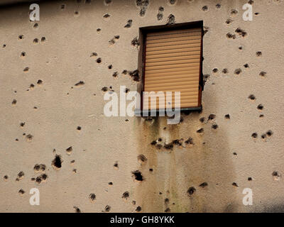 wall of building in Mostar pockmarked with missile shell and bullet holes around window after civil war in Bosnia - Stock Photo