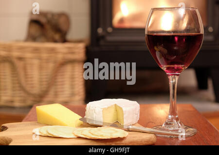 Cosy evening at home with red wine, brie or camembert cheese, crackers, in front of a fire in woodburner or wood - Stock Photo