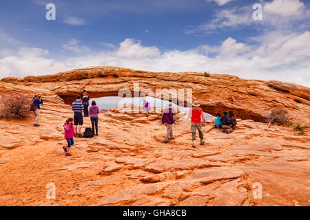 Tourists at Mesa Arch, a pothole arch in the Island in the Sky area of Canyonlands National Park, Utah, USA - Stock Photo