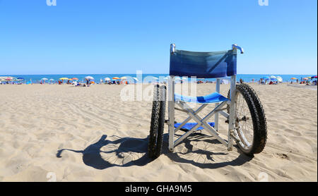 isolated wheelchairs for people with mobility problems on the sea beach - Stock Photo