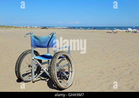 isolated wheelchairs for people with mobility problems on the sea beach in summer - Stock Photo