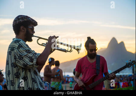 RIO DE JANEIRO - FEBRUARY 21, 2015: Silhouette of a musician playing his horn to an audience at the popular Arpoador - Stock Photo