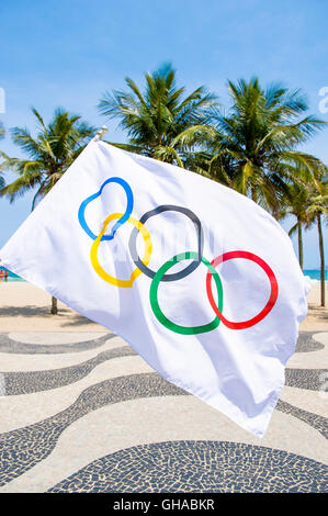 RIO DE JANEIRO - MARCH 10, 2016: Olympic flag waves in front of the iconic wave pattern of the sidewalk on Copacabana - Stock Photo