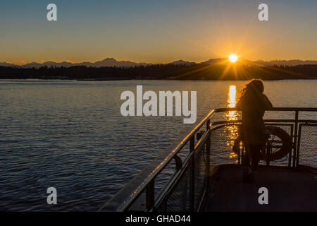 Young girl watching the sunset on the Elliott Bay from the ferry, Seattle, Washington, USA - Stock Photo