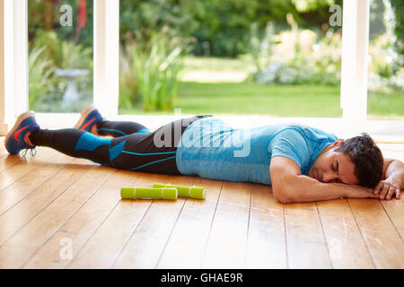Man laid out exhausted after exercising - Stock Photo