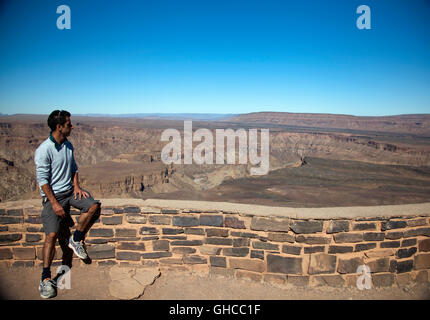 Man Looking over Fish River Canyon  in Namibia - Stock Photo