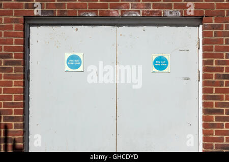 Fire exit doors in a brick building looking like a face with two blue eyes - Stock Photo