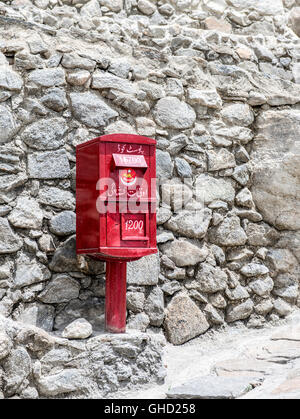 Red mail box in front of a stone wall in Pakistan - Stock Photo