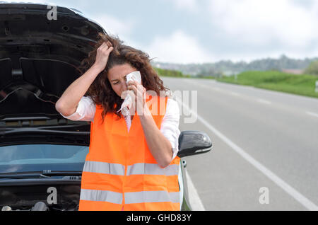Upset young woman crying after a car breakdown standing wiping tears from her eyes in front of the vehicle at the - Stock Photo