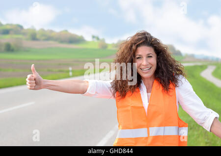 Smiling confident young woman wearing a high visibility jacket standing at the roadside hitching a lift after breaking - Stock Photo