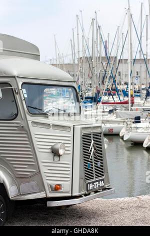 vintage Citroen H van in front of boats in a marina