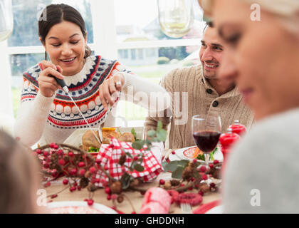 Woman cutting Christmas turkey at table - Stock Photo