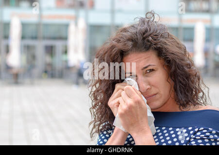 Tearful young woman wiping her eyes with a white handkerchief while looking at the camera with a melancholy expression - Stock Photo