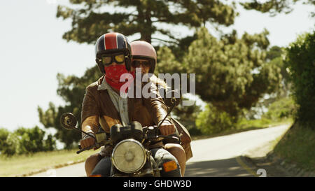 Young couple riding motorcycle on sunny road - Stock Photo
