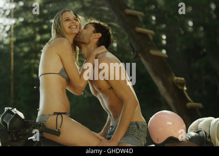 Young man kissing young woman in bikini on motorcycle - Stock Photo