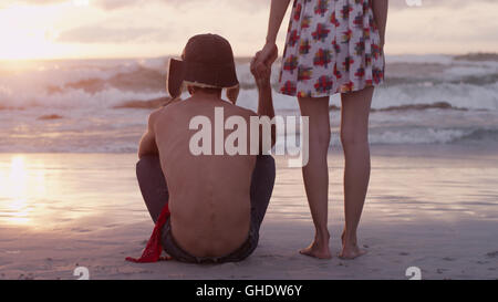 Young couple holding hands on beach at sunset - Stock Photo