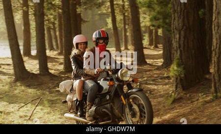 Young couple riding motorcycle in woods - Stock Photo