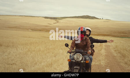 Exuberant young woman riding motorcycle in rural countryside - Stock Photo