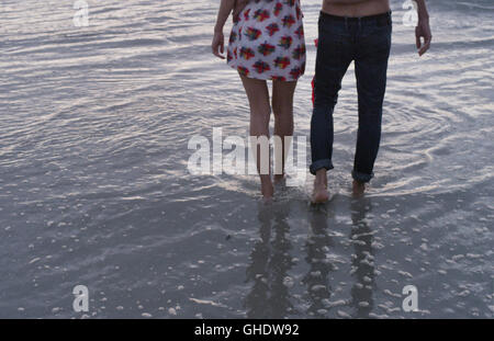 Young couple walking in ocean surf - Stock Photo