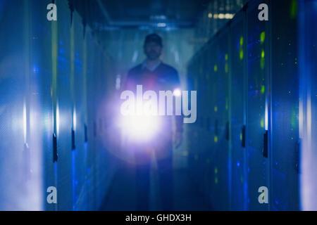 Server room technician with flashlight in dark corridor - Stock Photo