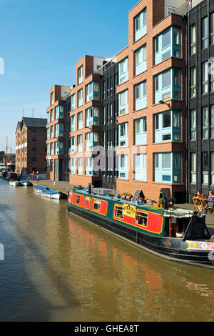 Canal boat cafe moored alongside new build apartments and shops in spring sunshine at Gloucester Docks, Gloucester, UK