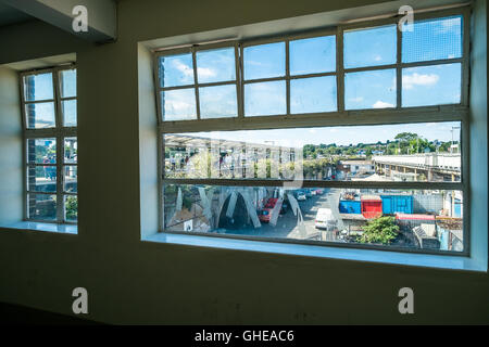 Through a window of Peckham Rye train station looking down onto the train tracks and arches below. - Stock Photo
