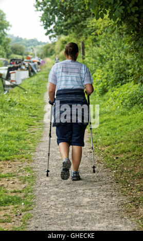 Walker using walking poles on towpath by canal - Stock Photo