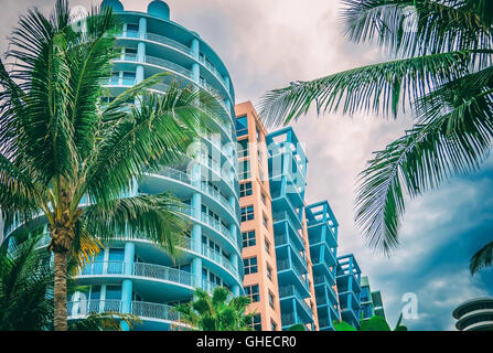 Modern residential buildings blue and apricot color with palm trees in Miami against blue sky background - Stock Photo