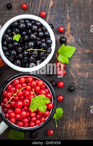 Fresh delicious organic red and black currants in a mugs on wooden table - Stock Photo