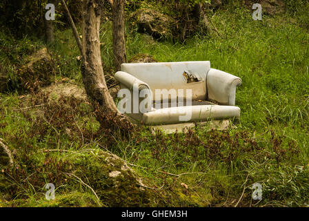 Old sofa dumped in a forest an example of fly tipping or illegal dumping - Stock Photo