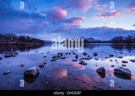 Pink and purple clouds over Derwentwater after sunset viewed from the northern shore near the town of Keswick - Stock Photo